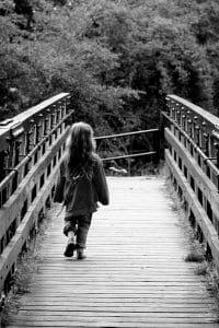 little girl walking across bridge